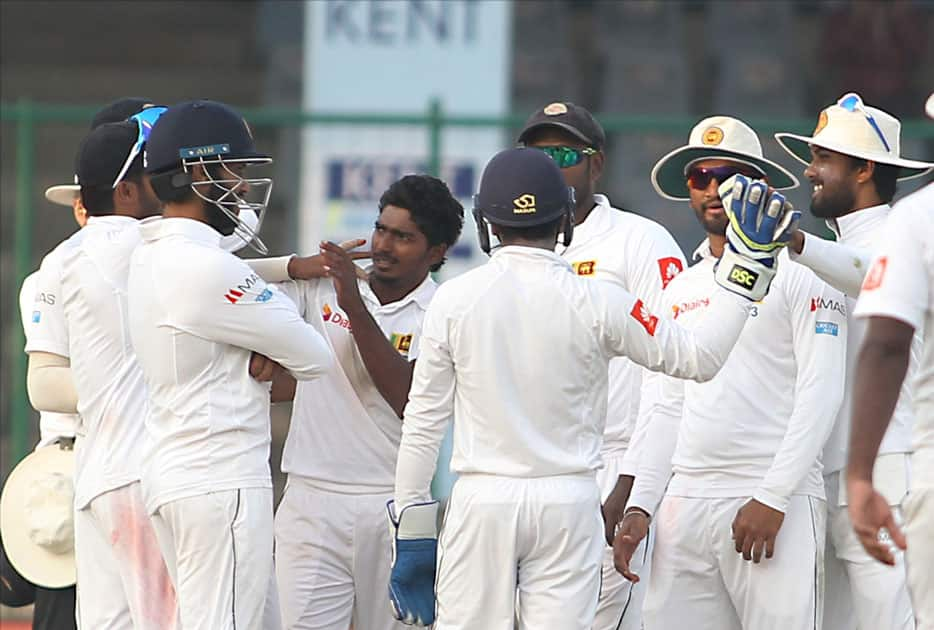 Sri Lanka's Lakshan Sandakan celebrates fall of a wicket of India's Ajinkya Rahane with teammates on Day 1 of the third test match between India and Sri Lanka at Feroz Shah Kotla Stadium in New Delhi.