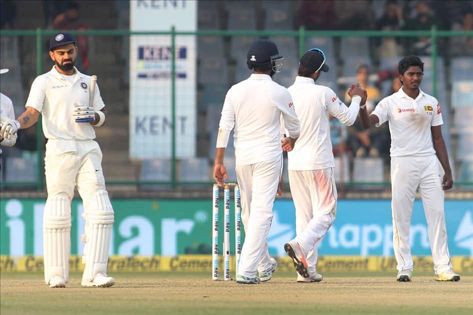 Sri Lanka's Lakshan Sandakan celebrates fall of a wicket of India's Murali Vijay with teammates on Day 1 of the third test match between India and Sri Lanka at Feroz Shah Kotla Stadium in New Delhi.