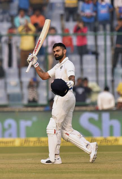 Indian skipper Virat Kohli raises his bat after scoring a century against Sri Lanka during the first day of third cricket test match at Feroz Shah Kotla, in New Delhi.