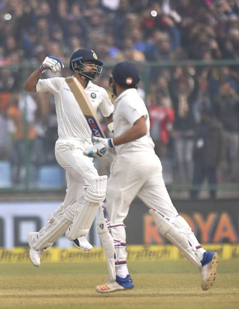 India's Virat Kohli exults after his double century against Sri Lanka as teammate Rohit Sharma looks on, during the second day of the third cricket test match at Feroz Shah Kotla, in New Delhi.