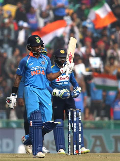 India's Shikhar Dhawan celebrates his half-century during the 2nd One Day International (ODI) match between India and Sri Lanka at Punjab Cricket Association IS Bindra Stadium in Mohali.