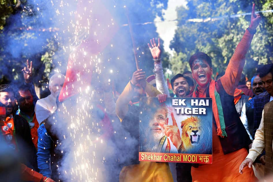 Party workers and supporters celebrating BJP's success in the state assembly elections outside the BJP headquarter, in New Delhi.