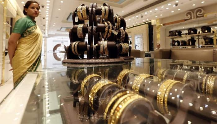 Gold falls to Rs 31,570 on weak global cues, muted demand