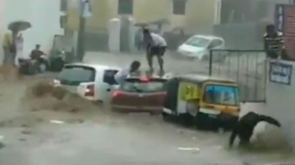 Watch: Two cars get washed away on flooded street moments after narrow escape for occupants
