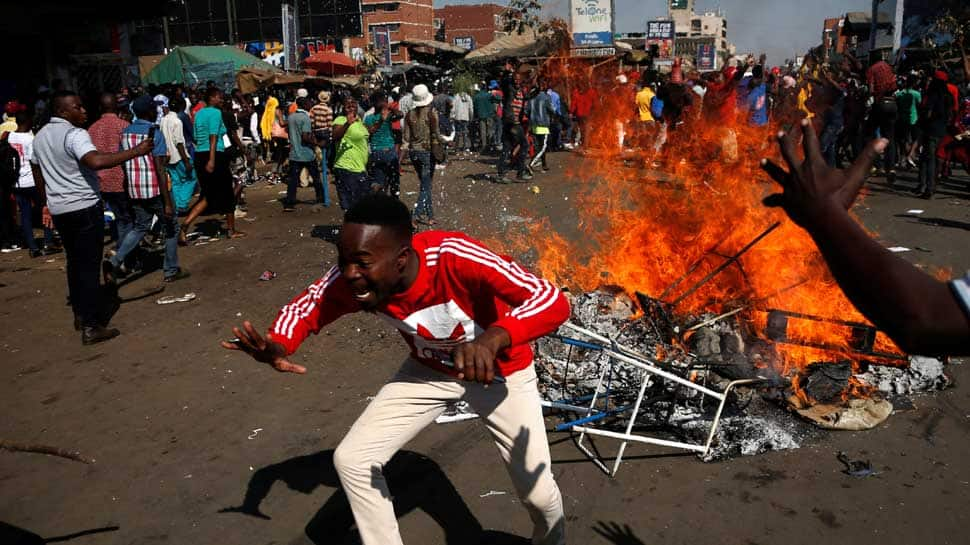 Opposition protesters clash with police as ruling party wins majority in Zimbabwe, one dead