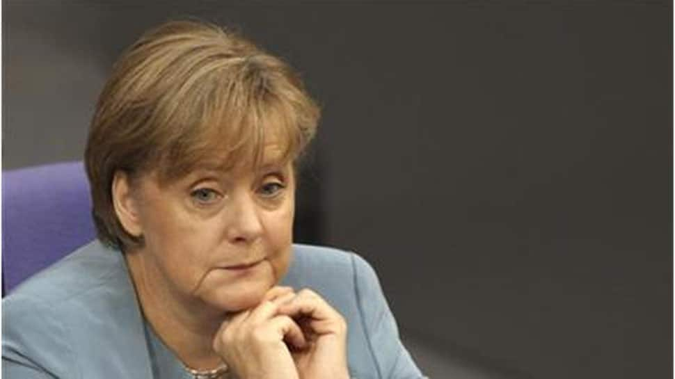 Merkel sits rather than stands at public ceremony, following shaking bouts