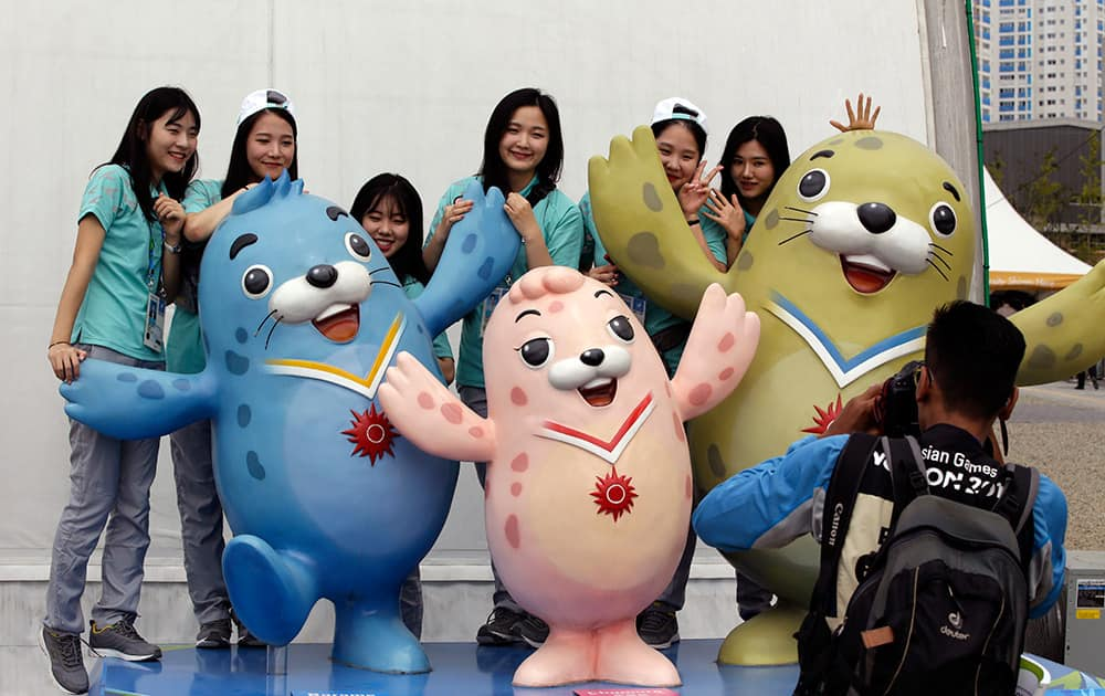 Volunteers pose for photos near three official mascots of the the 2014 Incheon Asian Games, near the 17th Asian Games Athletes' Village in Incheon, west of Seoul, South Korea.