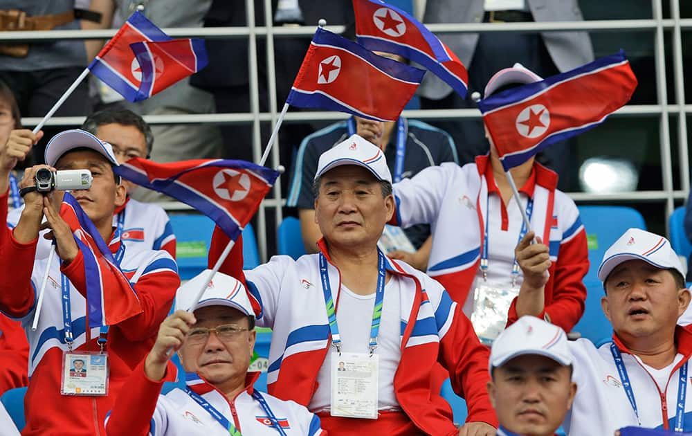 North Korea's team officials wave their national flags during their first round soccer match against China at the 17th Asian Games in Incheon, South Korea.