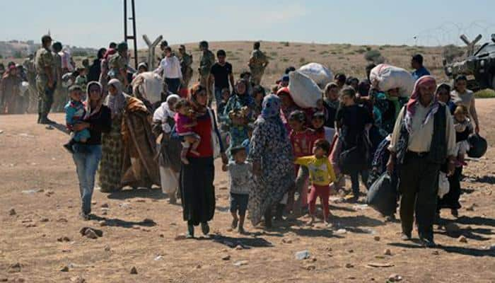 Thousands of Syrian Kurds flee from ISIS militants into Turkey