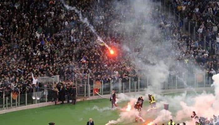 VIDEO: Fire in dug-out – Watch football fans firing flares at rival camp