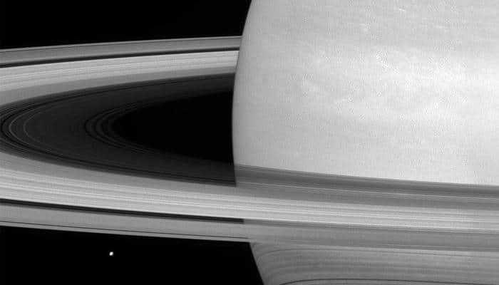 Saturn's icy moon 'Mimas' dwarfed by huge rings