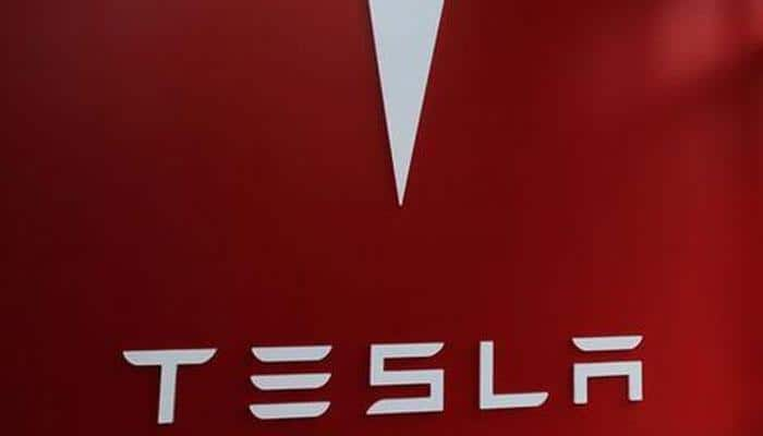 Tesla's Elon Musk hands over first Model 3 electric cars to early buyers