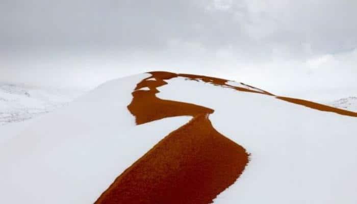 Snow paints red sand dunes of Sahara desert a wondrous white