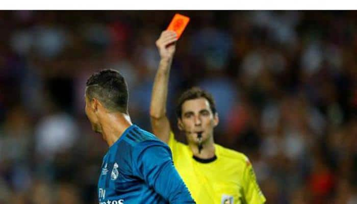 Football referees watching slow motion videos flash more red cards