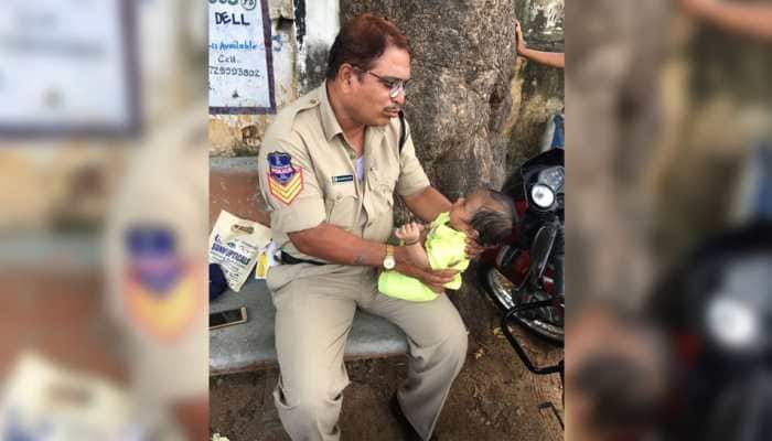 Cop babysits crying baby as mother writes exam; heartwarming photo goes viral