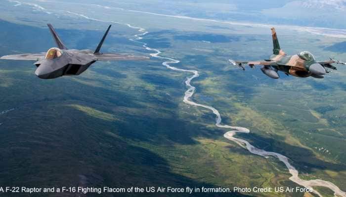 US Air Force F-22 Raptors and F-16 Fighting Falcons fly in formation