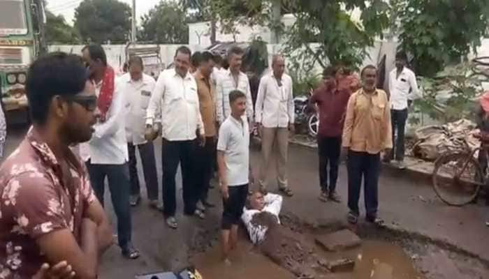 Potholes as bed: Rajkot man lies on broken roads to protest civic apathy