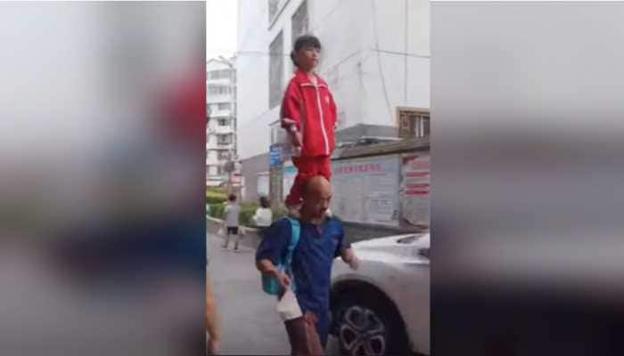 Watch: Chinese girl balances on grandfather's shoulders while on her way to school